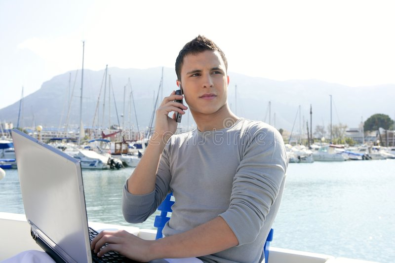 Businessman working with computer on a boat royalty free stock photography