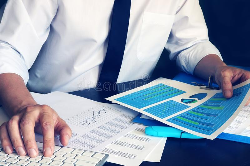 Businessman working with computer and financial business documents. stock photo