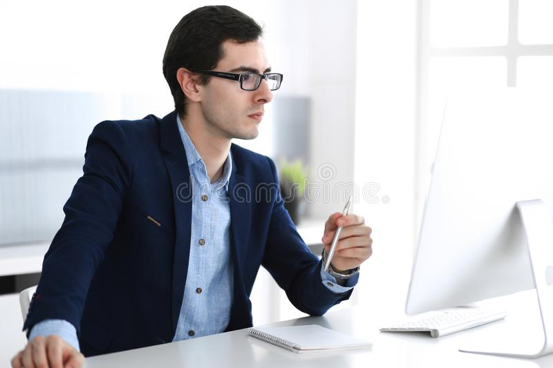 Businessman working with computer in modern office. Headshot of male entrepreneur or company manager at workplace royalty free stock photo