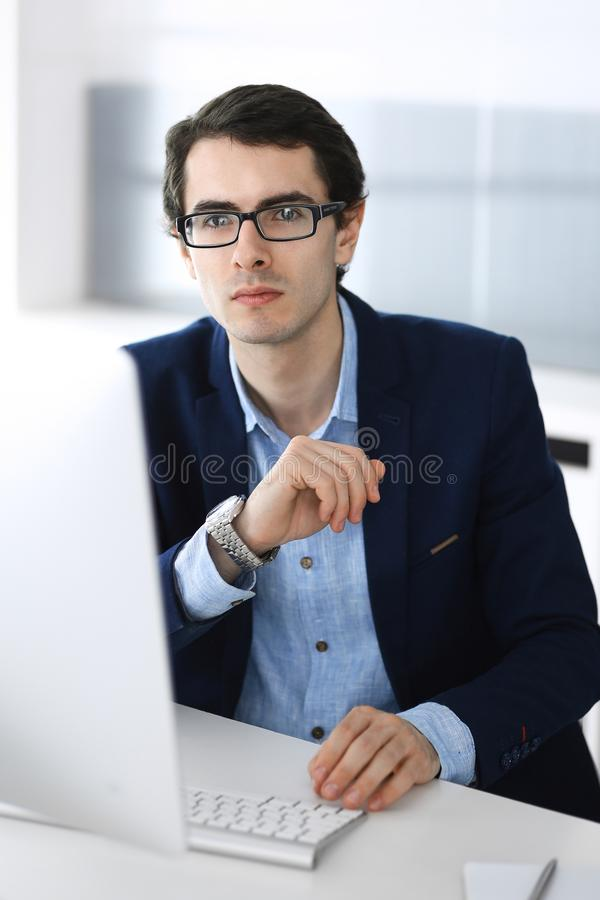Businessman working with computer in modern office. Headshot of male entrepreneur or company manager at workplace royalty free stock images