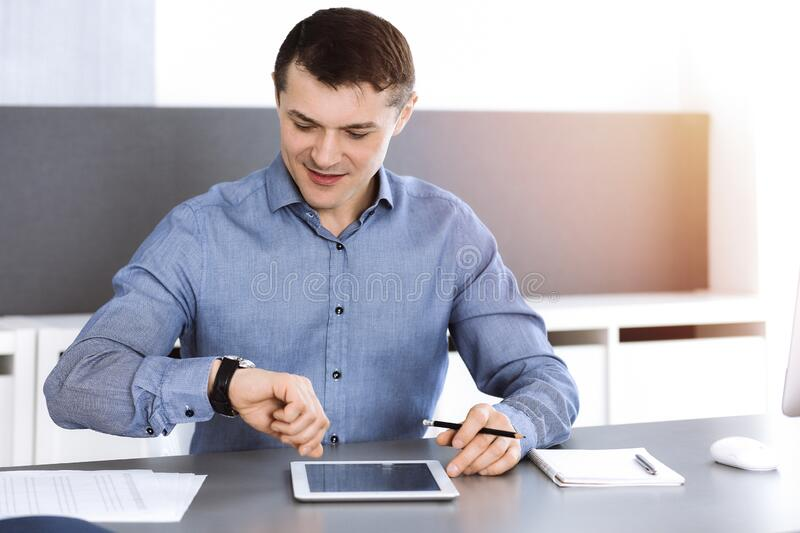 Businessman working with computer in modern sunny office. Headshot of male entrepreneur or company director at workplace. Business concept stock photography