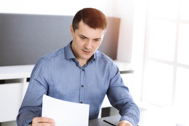 Businessman working with computer in modern sunny office. Headshot of male entrepreneur or company director at workplace. Business concept royalty free stock image
