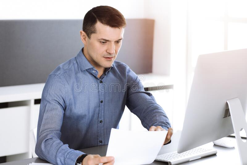 Businessman working with computer in modern sunny office. Headshot of male entrepreneur or company director at workplace. Business concept royalty free stock photography