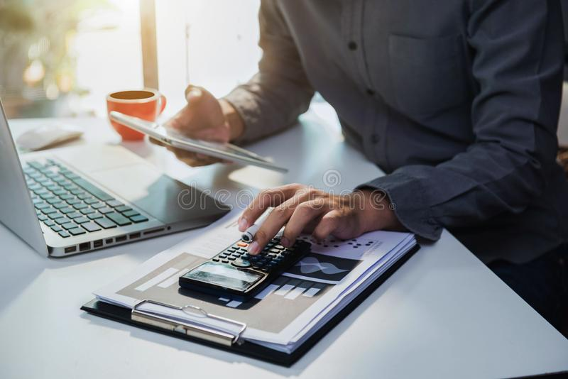Businessman working on desk office with using a calculator and tablet to calculate. stock images