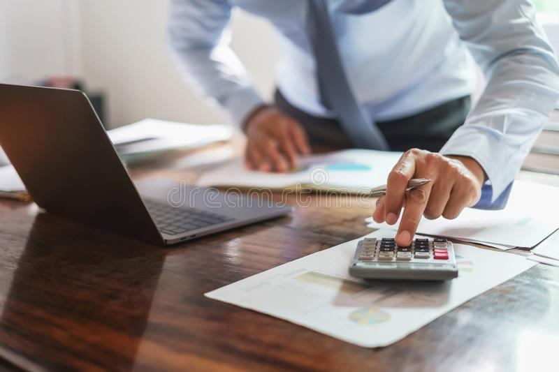 Businessman working on desk office with using a calculator to calculate money report, finance accounting concept. Development, payment, workplace, strategy royalty free stock photos