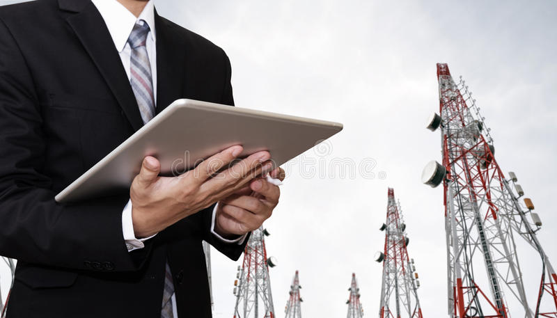 Businessman working on digital tablet, with satellite dish telecom network on telecommunication tower in the morning stock photo