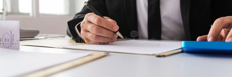 Businessman working on financial paperwork stock photo