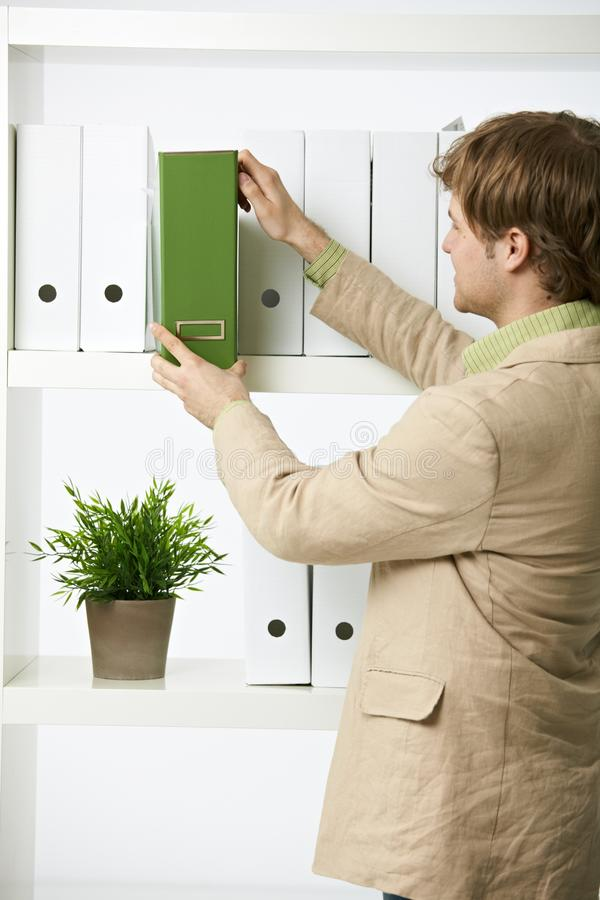 Businessman working in green office. Businessman drawing out green folder in office royalty free stock photography