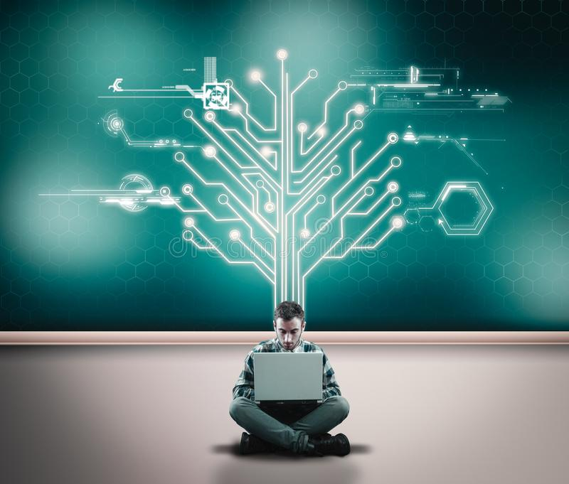 Businessman working on his laptop in front of a wall with a circuit board tree royalty free stock photography