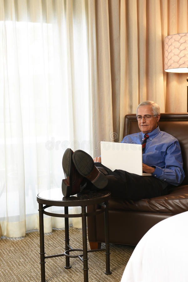 Businessman Working in Hotel Room. A senior businessman seated on the couch of his hotel room with his feet up while he works on his laptop computer royalty free stock image
