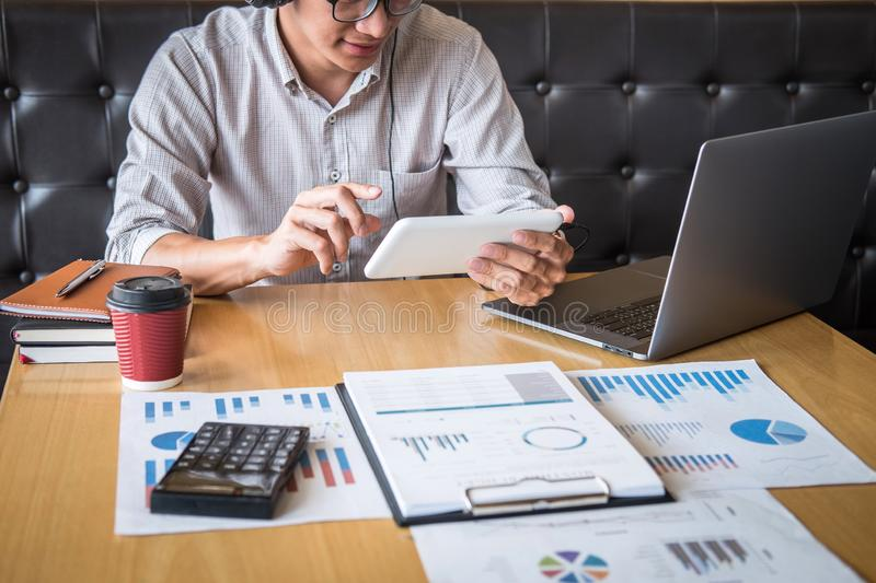 Businessman working investment project on laptop computer with report document and analyze, calculating financial data on graph. Documents, doing finance making stock photo