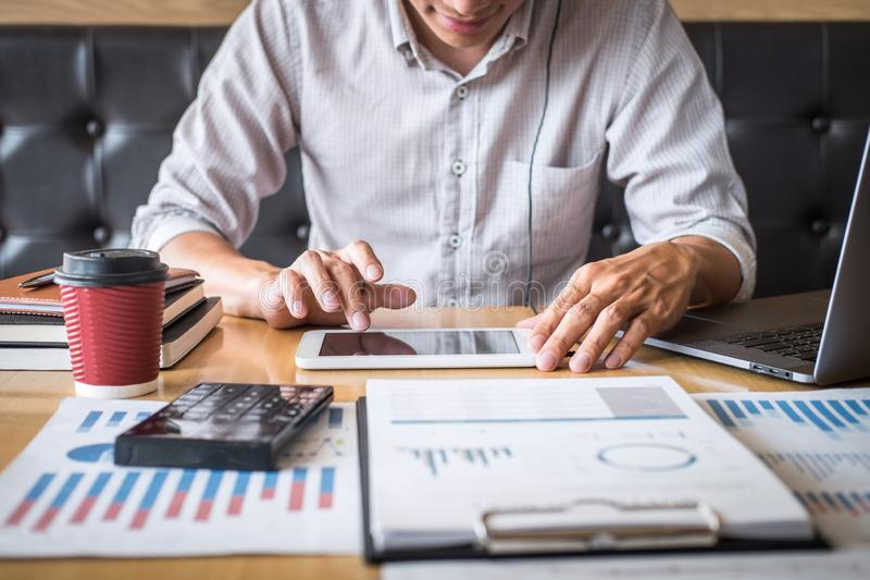 Businessman working investment project on laptop computer with report document and analyze, calculating financial data on graph. Documents, doing finance making royalty free stock image