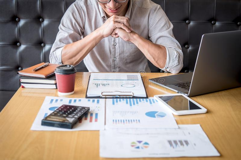 Businessman working investment project on laptop computer with report document and analyze, calculating financial data on graph. Documents, doing finance making royalty free stock photo