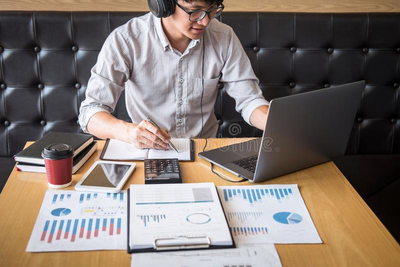 Businessman working investment project on laptop computer with report document and analyze, calculating financial data on graph. Documents, doing finance making stock image