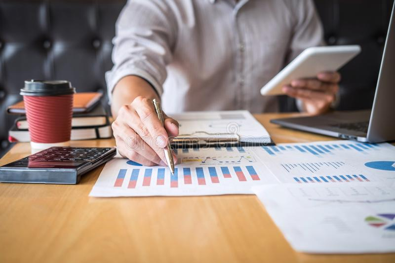 Businessman working investment project on laptop computer with report document and analyze, calculating financial data on graph. Documents, doing finance making royalty free stock photos
