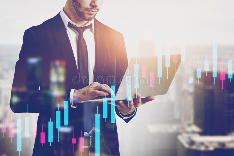 Man with laptop in city, financial graph stock photography