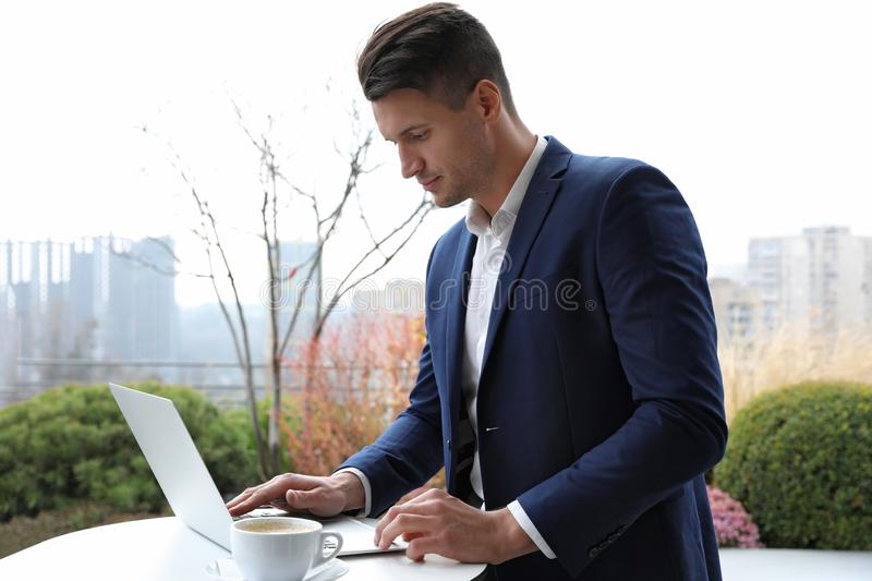 Businessman working with laptop in cafe. Corporate blog. Businessman working with laptop in outdoor cafe. Corporate blog royalty free stock image