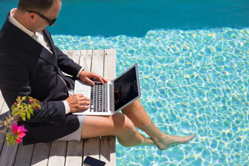 Businessman working with laptop computer by the pool stock photography