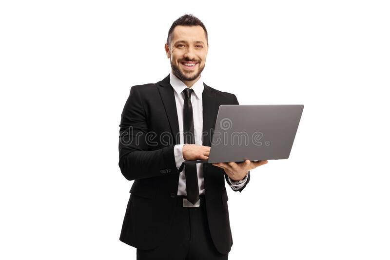 Businessman working on a laptop computer and smiling at the camera royalty free stock photography