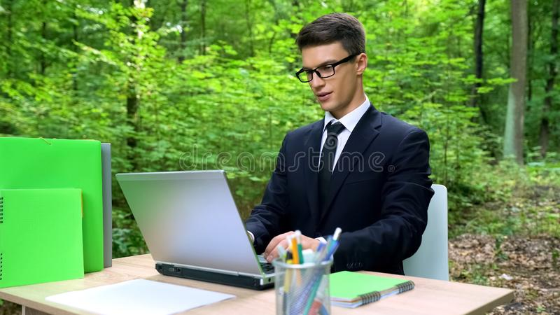 Businessman working on laptop in forest, inspired by nature beauty, ecology royalty free stock photo