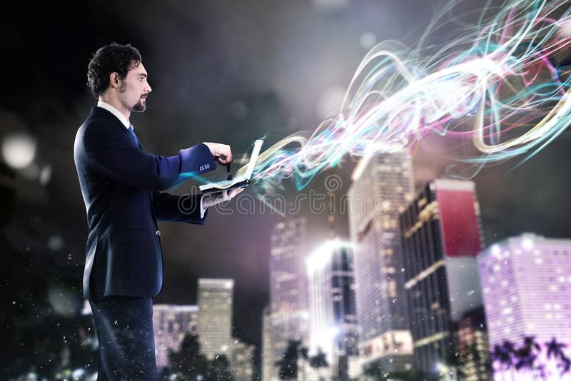 Businessman working on laptop with new connections. Businessman working with laptop with light effects on the city background. Work with new connections concept stock photography