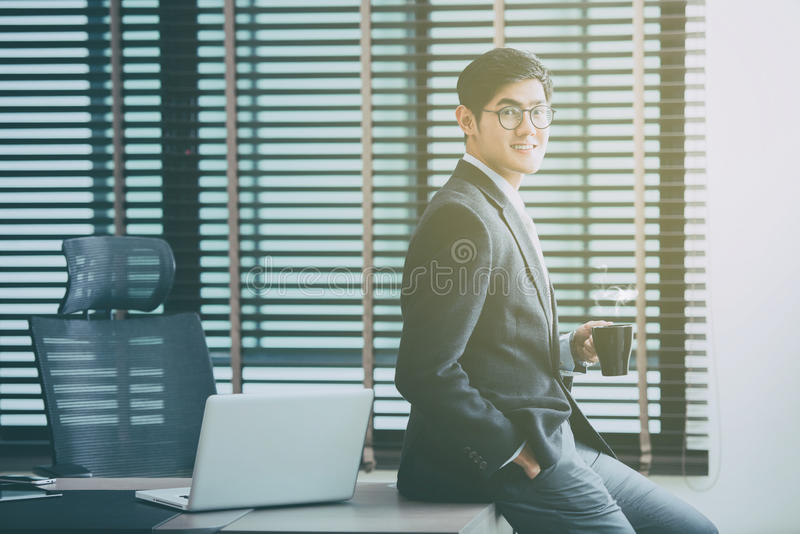 Businessman working on laptop in office, holding a cup of coffee stock image