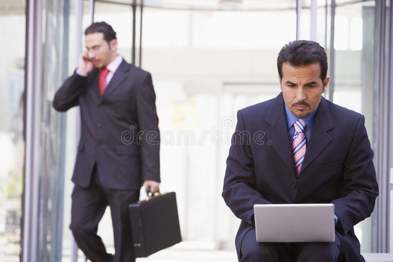 Businessman working at laptop outside stock photo