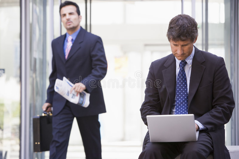 Businessman working at laptop outside royalty free stock image