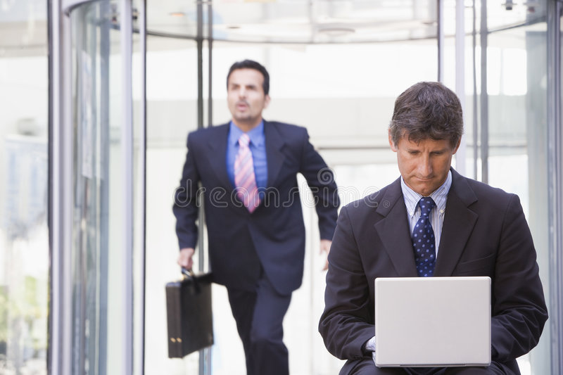 Businessman working at laptop outside stock image