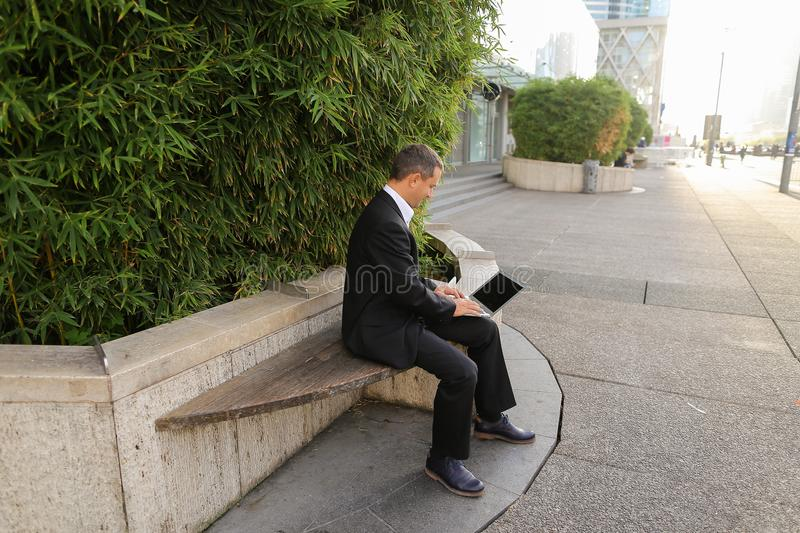 Businessman working with laptop outside near plant in . Businessman typing by laptop outside near green plant in and looking at watch. Concept of ecology stock images