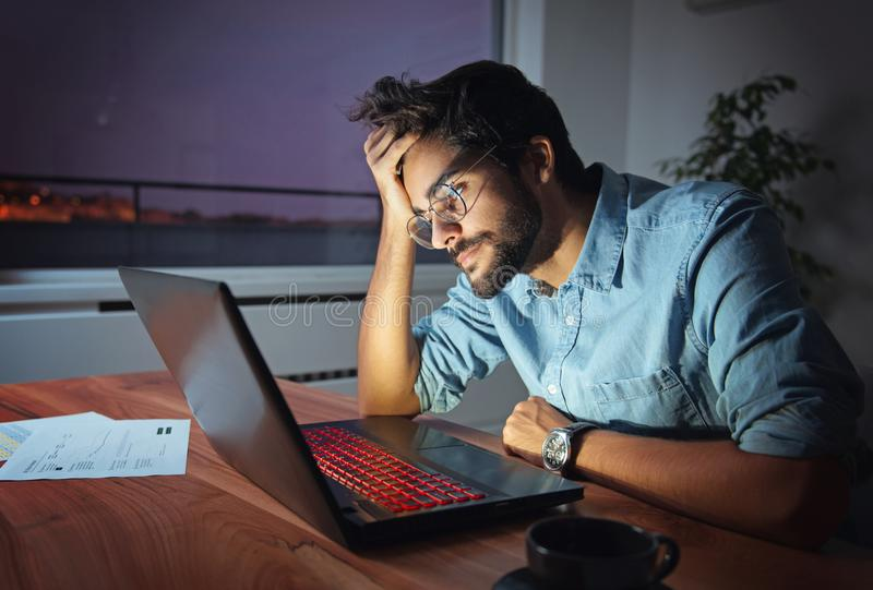 Businessman working on a laptop, overworking, under pressure. Tired and sleepy royalty free stock images
