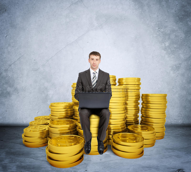 Businessman working on laptop. And sitting coins on grey wall background stock images