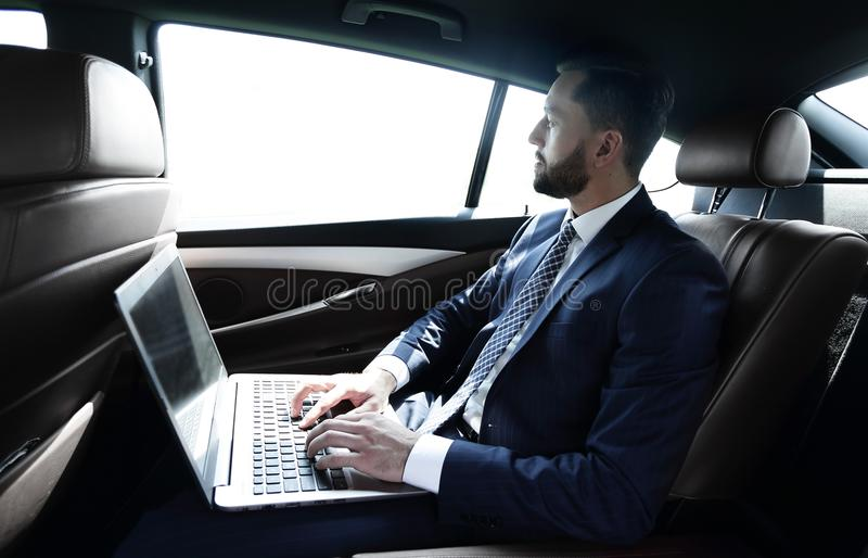 Businessman working with laptop sitting in car royalty free stock images
