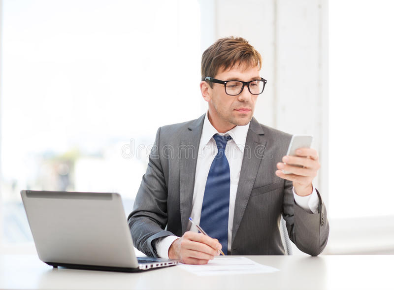 Download Businessman Working With Laptop And Smartphone Stock Photo - Image of eyeglasses, call: 35131440