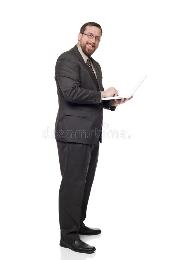 Businessman working on laptop while standing. Isolated full length studio shot of the side view of a businessman working on a laptop he is holding while standing stock images