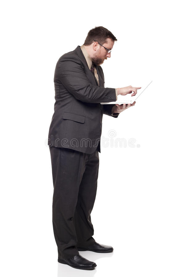 Businessman working on laptop while standing. Isolated full length studio shot of the side view of a businessman working on a laptop he is holding while standing stock image