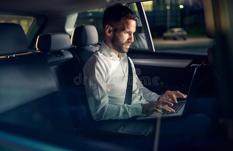 Businessman working late in car on laptop. In back seat royalty free stock photo