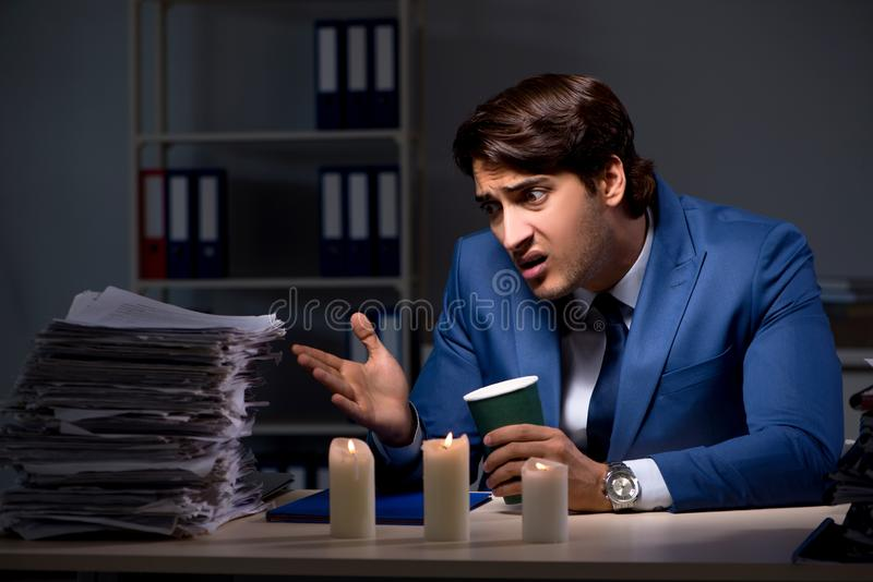 The businessman working late in office with candle light. Businessman working late in office with candle light stock photos