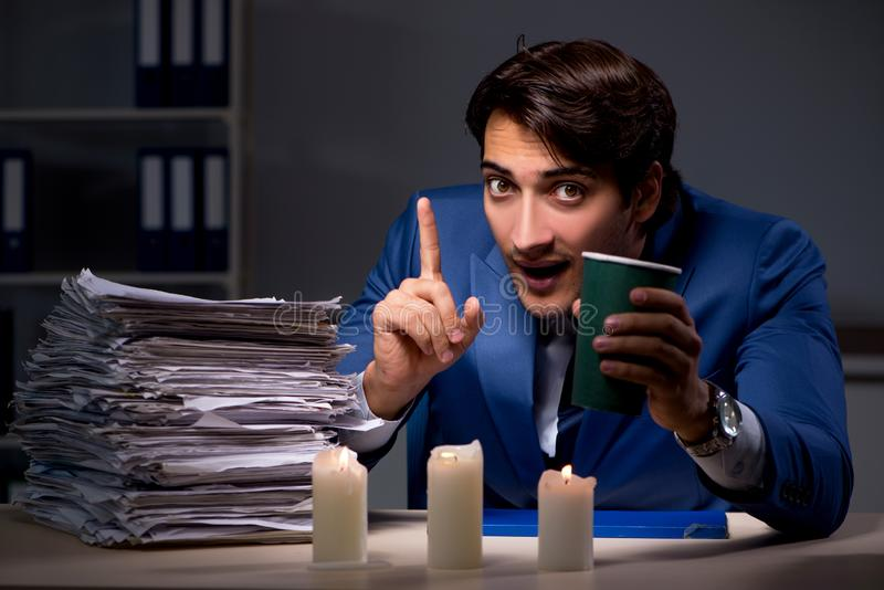 The businessman working late in office with candle light. Businessman working late in office with candle light stock image