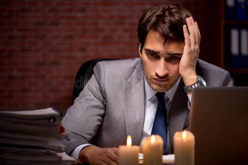 The businessman working late in office with candle light. Businessman working late in office with candle light stock photo