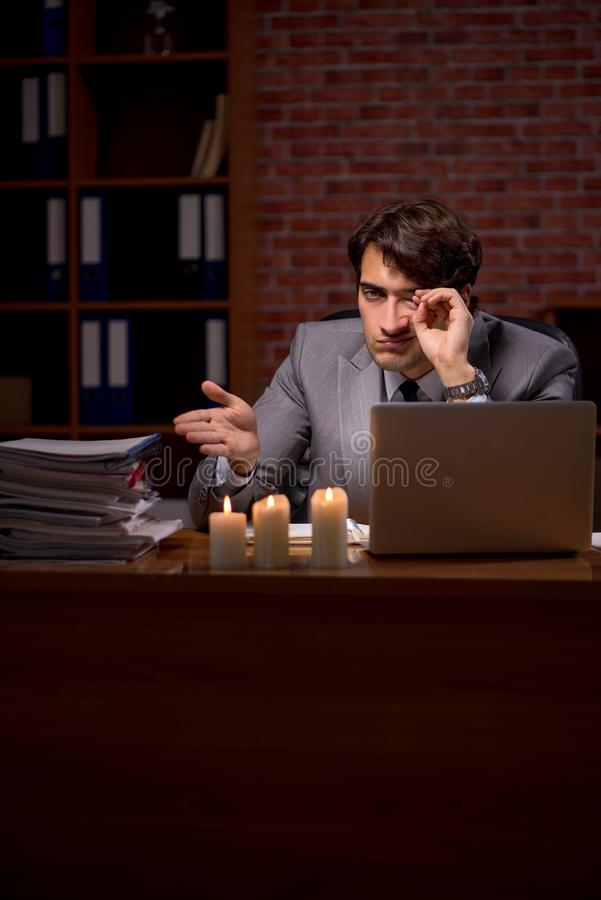 The businessman working late in office with candle light. Businessman working late in office with candle light stock photography