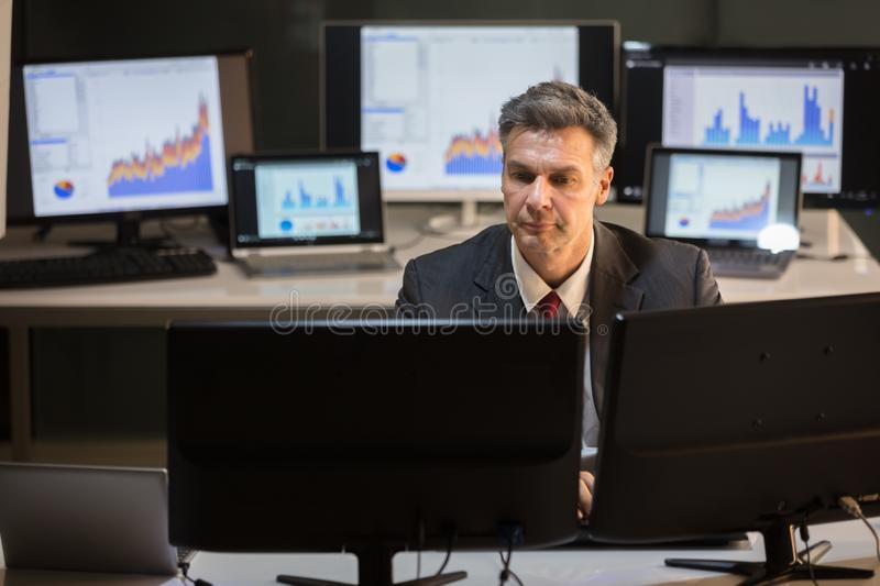 Businessman Working On Multiple Computer. Serious Mature Businessman Working On Multiple Computer At Workplace royalty free stock image