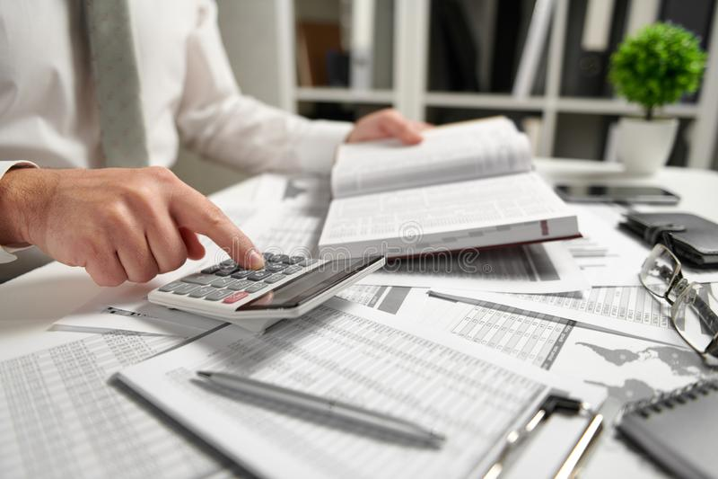 Businessman working at office and calculating finance, reads and writes reports. Business financial accounting concept stock images