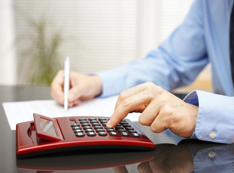 Businessman working in office with calculator and fulfilling do royalty free stock photography