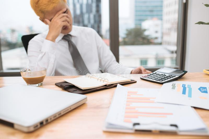 Businessman working on office desk, looking tired stock images