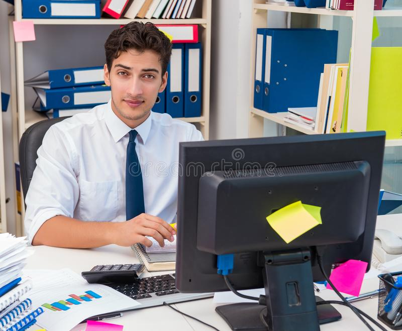 Businessman working in the office with piles of books and papers. Doing paperwork royalty free stock images