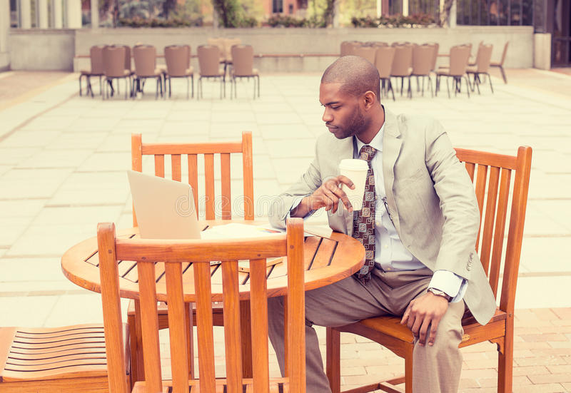 Businessman working outdoors with documents drinking coffee royalty free stock photo