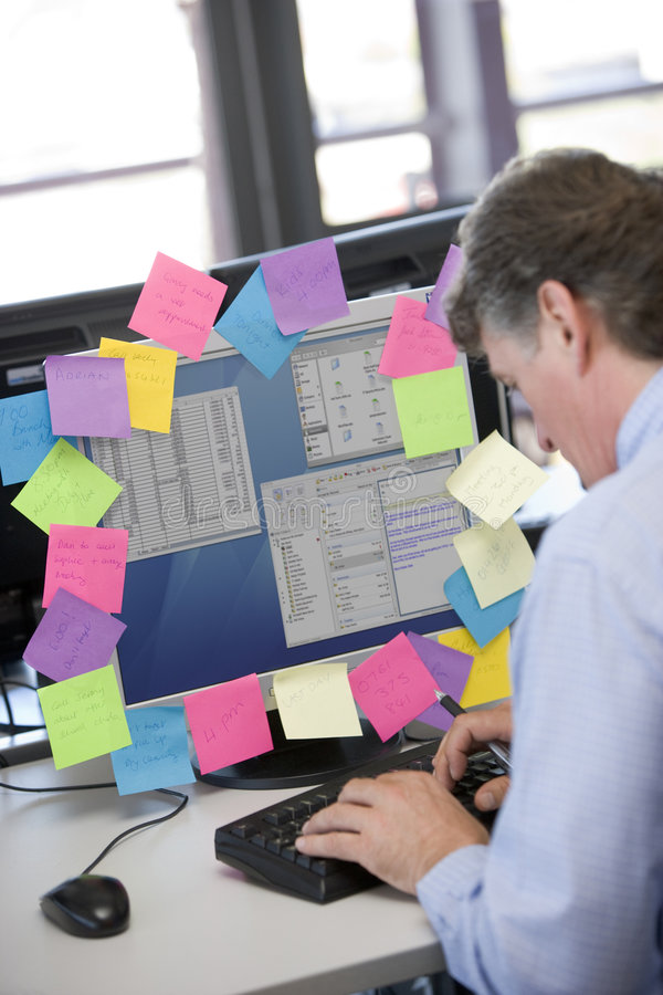 Businessman working at pc covered in reminders