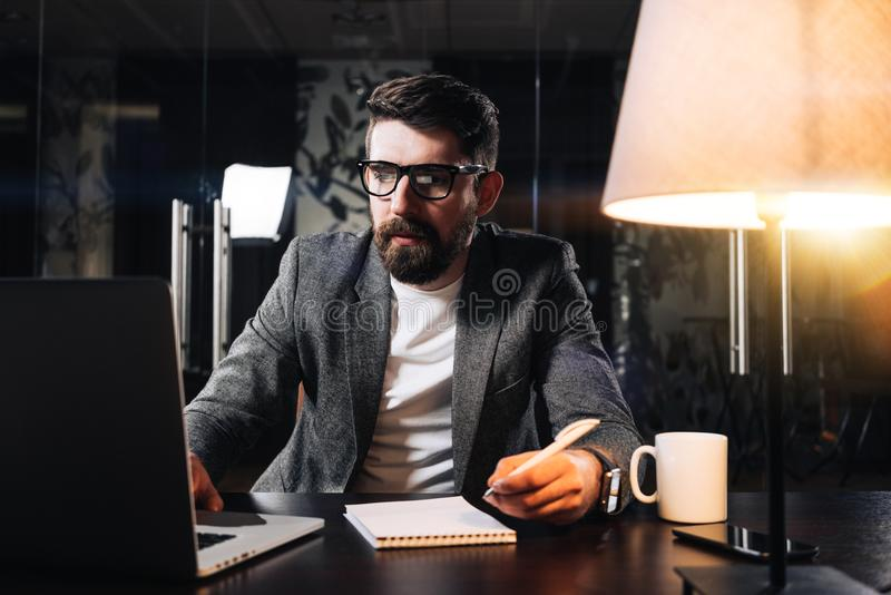 Businessman working process at open space office at night. Bearded coworker using modern laptop and sits by the wooden table with royalty free stock photo
