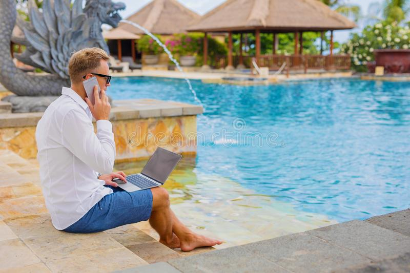 Businessman working while on vacation. Handsome businessman working while on vacation, sitting by the pool royalty free stock photography